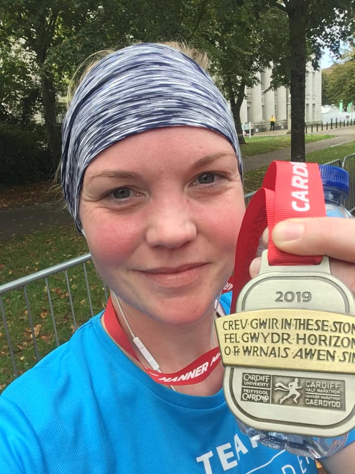 Sandra Johnson holding her Cardiff Half Marathon Medal